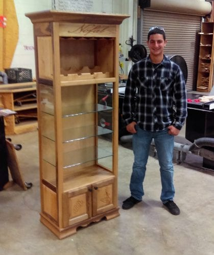 Boy in wood shop with cabinet