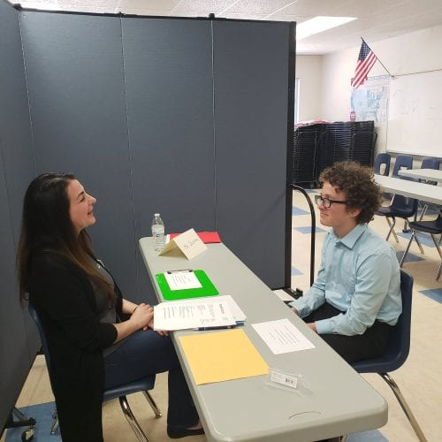 Student talking to teacher at desk